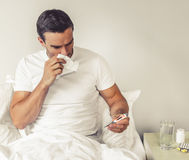 Man with common cold. Handsome man affected by common cold is looking at the thermometer and wiping nose with paper tissue while sitting in bed at home Stock Images