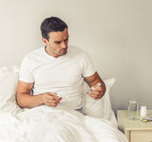 Man with common cold. Handsome man is having a common cold. He is holding a thermometer and paper tissue while sitting in bed at home Royalty Free Stock Photos