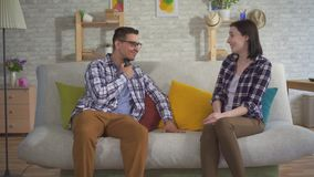 A man communicates with a young woman sitting on the couch uses Speech Aid