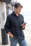 Man communicating with smart phone at beach. Handsome Caucasian man in casual clothes next to pier at beach on cloudy day smiles as he reads message on his smart Royalty Free Stock Photography