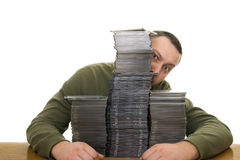 Man with compact disc. Man holding a pile of CD on the table Stock Image