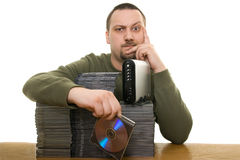 Man with compact disc. Man holding a pile of CDs on the table Stock Image