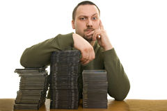 Man with compact disc. Man holding a pile of CDs on the table Royalty Free Stock Photos