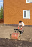 Man compacts soil with hand metal roller Stock Images