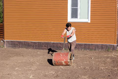 Man compacts soil with hand metal roller Royalty Free Stock Photo