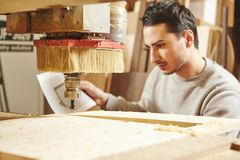 Man compares the CNC machine with the drawing. Device with numerical control. Woodworking industry stock images