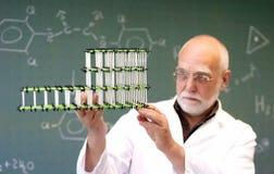 Man compares two molecular models. Professor examines a model molecule in the classroom Royalty Free Stock Photos