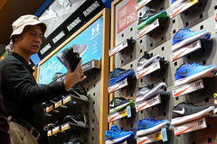 Man comparing two pair of exposition sport shoes Royalty Free Stock Photography