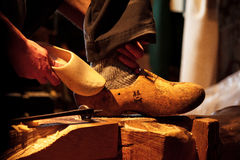 Man comparing wooden shoes. Wooden shoe making device in historical small dutch village Zaanse Schans. Man compares the quality of the shoes Stock Photos