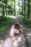 Man with compass in hand. In lush summer forest. Travel concept stock photography