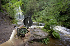 Man with compass near waterfall Stock Photos