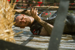 Man competing in obstacle course and mud run. A participant in the Gladiator Rock-n-Run event at the Rose Bowl in Pasadena in 2014. Competitors must run, slide royalty free stock photo