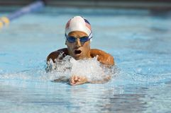 Man Competing In Swimming Race. Front view of a Caucasian swimmer in motion during swimming race Royalty Free Stock Photos