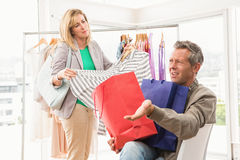 Man complaining about his shopping woman. Man complaining about his shopping women in clothing store Royalty Free Stock Photos