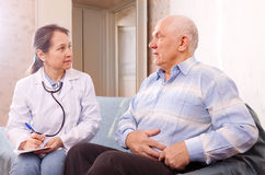 Man complaining to doctor about stomachache stock images