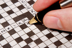 Man completing crossword. Close-up of a man' s hand filling in a crossword puzzle Stock Photography