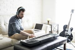 Man composing a song with electric piano. Handsome young man playing music and composing a song with electric piano while sitting in living room at home royalty free stock image