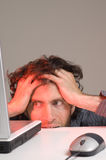 Man and computer. Man looking at computer screen holding hair in frustration Stock Image