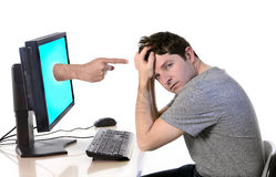 Man with computer accusing finger cyberbullying. Young attractive man in stress and worried with computer finger pointing in social media network cybermobbing Stock Photos