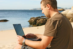 Man with computer at beach Royalty Free Stock Photos