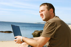 Man with computer at beach Stock Images