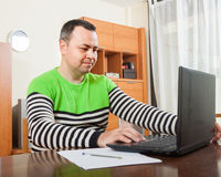 Man at computer in home stock images