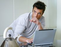 Man with computer in kitchen Stock Images