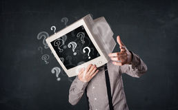 Man with a computer monitor head and question marks Stock Photography