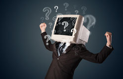 Man with a computer monitor head and question marks Royalty Free Stock Photography