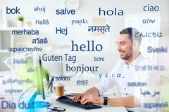 Man with computer over words in foreign languages. Translation, business, and technology concept - smiling male translator or businessman typing on computer stock photography