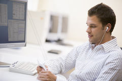 Man in computer room listening to MP3 player. Looking at it Royalty Free Stock Image