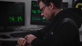 The man in the computer room. Young man with glasses looking closely at their apple watch, and also makes viewing stock video footage