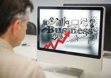 Man at computer showing red arrow with black business doodles against blurry background Royalty Free Stock Photography