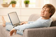 Man with computer on sofa Royalty Free Stock Photos