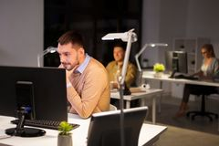 Man with computer working late at night office. Business, deadline and technology concept - men with computer working at night office stock photography