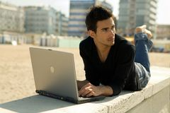Man with computer working outd. Attractive young man working at the beach with a laptop Stock Photo