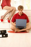 Man concentrating on work. Young man concentrating on computer work at home, woman sitting in seductive red baby-doll and slippers royalty free stock photo