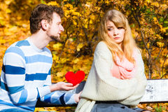 Man confess love to girl on bench in park. Confessing love and affection with romantic gesture. Rejection and disapproval. Negative reaction. Pair sit on bench Stock Photos