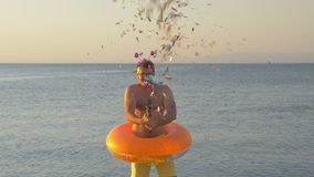 Man with confetti cracker at the seaside. Slow motion clip of a young man wearing funny ears and rubber ring making confetti firework with a cracker. Celebration stock video footage
