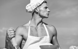Man on confident face wears cooking hat and apron, sky on background. Cookery concept. Chef cook preparing dough for. Baking. Cook or chef with muscular royalty free stock photos
