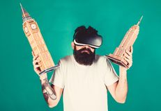 Man on confused face study architecture or design in virtual reality. Guy in VR glasses holds Big Ben and Empire State. Building. 3D design concept. Man with royalty free stock image