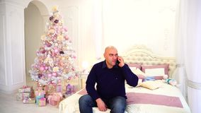Man congratulates relatives on phone with New Year`s holidays with sons, sitting on bed in bedroom with festive stock footage