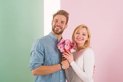 Man congratulates woman birthday anniversary holiday, pastel background. Gift concept. Couple date bouquet flowers gift stock photography