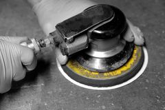 Man connecting air hose to orbital sander Royalty Free Stock Photography