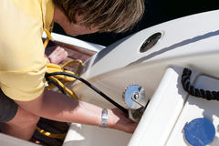 Man Connecting Power Cord To The Boat. Man connecting power cord to inlet of boat stock image