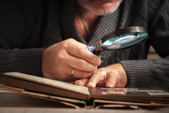 Man consider something trough the magnifying glass. Man considers album of stamps trough the magnifying glass horizontal Royalty Free Stock Image