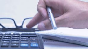Man considers on the calculator and making notes in a notebook stock video footage