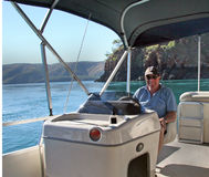 Man at Console of Party Pontoon. Portrait view of mature man sitting at console of modern party pontoon boat against a background of turquoise sea, cliff and stock images