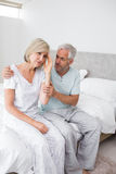 Man consoling tensed woman in bed Royalty Free Stock Photo