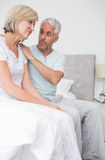 Man consoling tensed woman in bed Stock Image